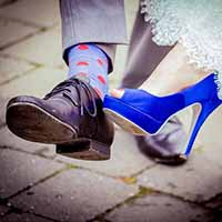 Bride and groom showing of their shoes.